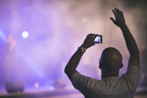 man taking a picture at a concert