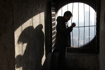 man standing in prayer in front of a barred window