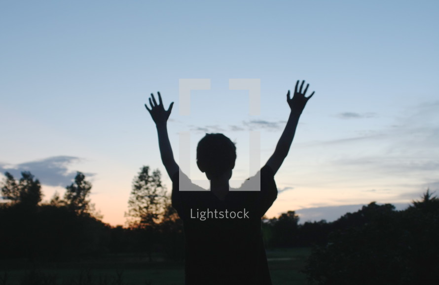 silhouette of a boy with his hands raised