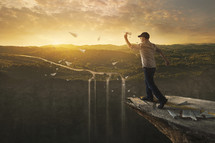 a man throwing paper airplanes off the edge of a cliff