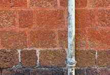 brick wall with rusted water pipe