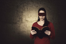 A blind folded woman reading a Bible.