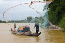 Nomadic fisherman casting a throw net to catch fish