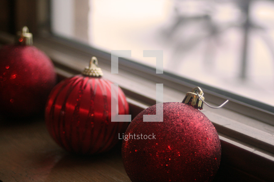 Red Christmas balls sitting on a windowsill.