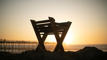 manger on a beach at sunset