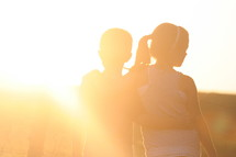 children hugging under bright sunlight