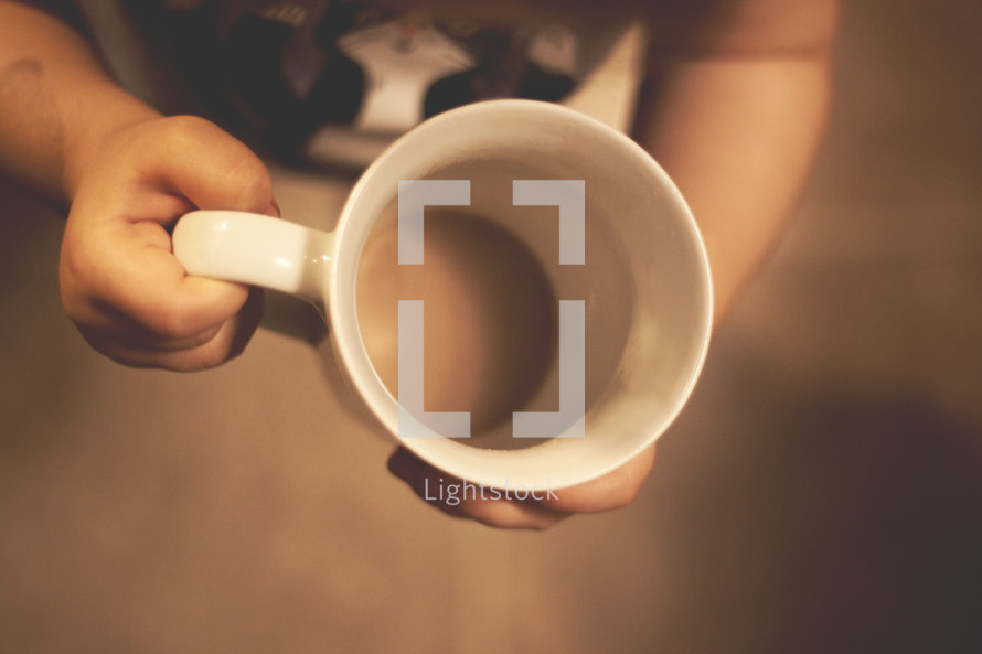 a toddler holding an empty mug