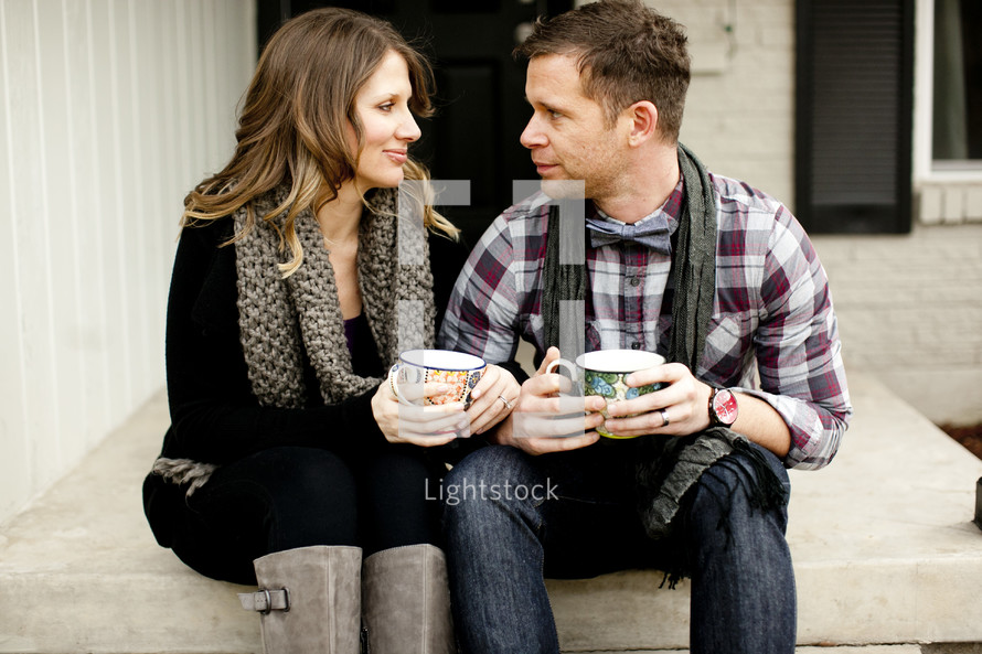 couple sitting on a step holding mugs of coffee