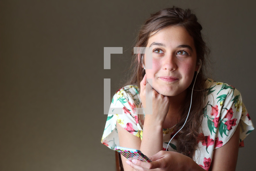 A teenage girl listening to music with earphones.