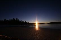The sun setting beyond a lake.