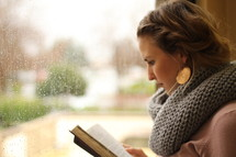 a woman reading a Bible and rain out a window