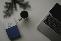 A Bible, computer, and cup of coffee on a white surface.