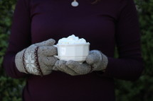 a woman in gloves holding a mug of hot cocoa