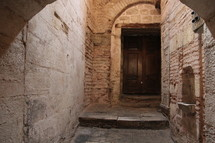 Wooden door at then end of an arched stone hallway.