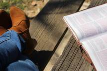 a woman's boots and an open Bible
