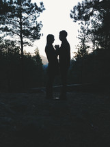 Silhouette of embraced couple outside at dusk.
