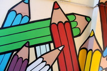 Painted mural of children's rainbow coloring crayons