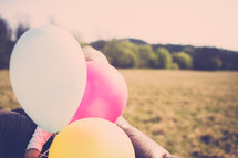 child holding balloons