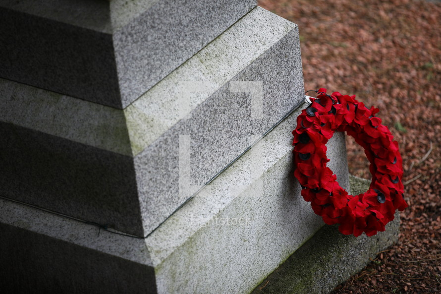 A red funeral wreath on a cemetery headstone.