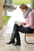 a woman sitting on a bench outdoors reading a Bible in the rain
