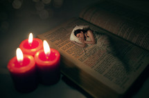 Candles lighting a woman sleeping on a bed superimposed on a Bible.