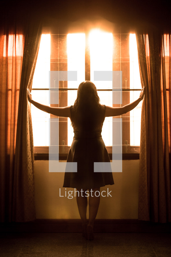 a woman pushing open curtains to look out a window