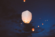 paper lanterns floating in the night sky