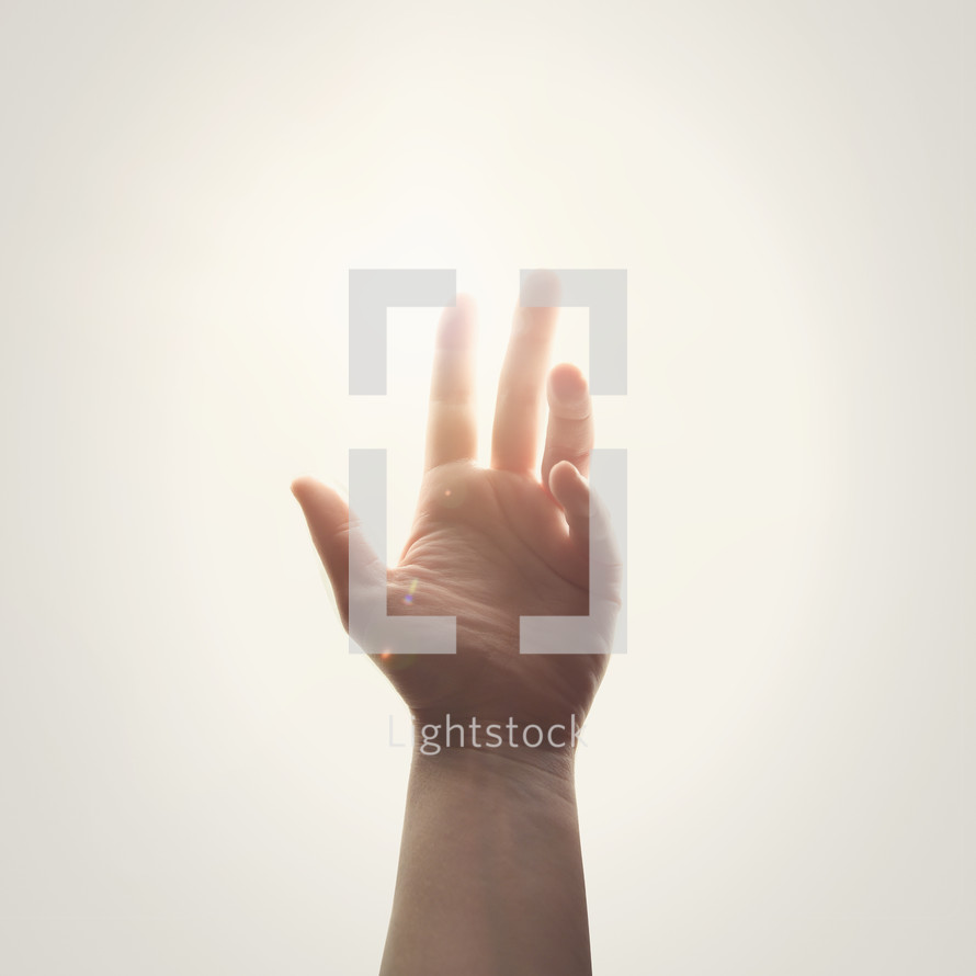 raised hand in glowing sunlight