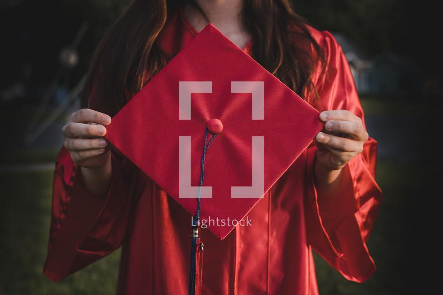 graduate holding a graduation cap