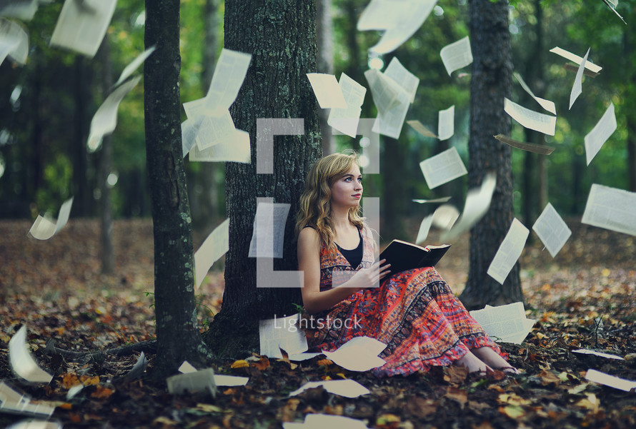 pages of a Bible raining down on a woman reading a Bible