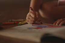 a child coloring in a coloring book with crayons