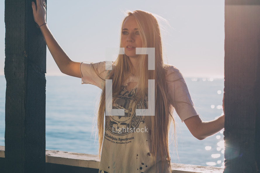 woman with long blonde hair standing near water