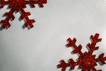red snowflake ornaments on a red background