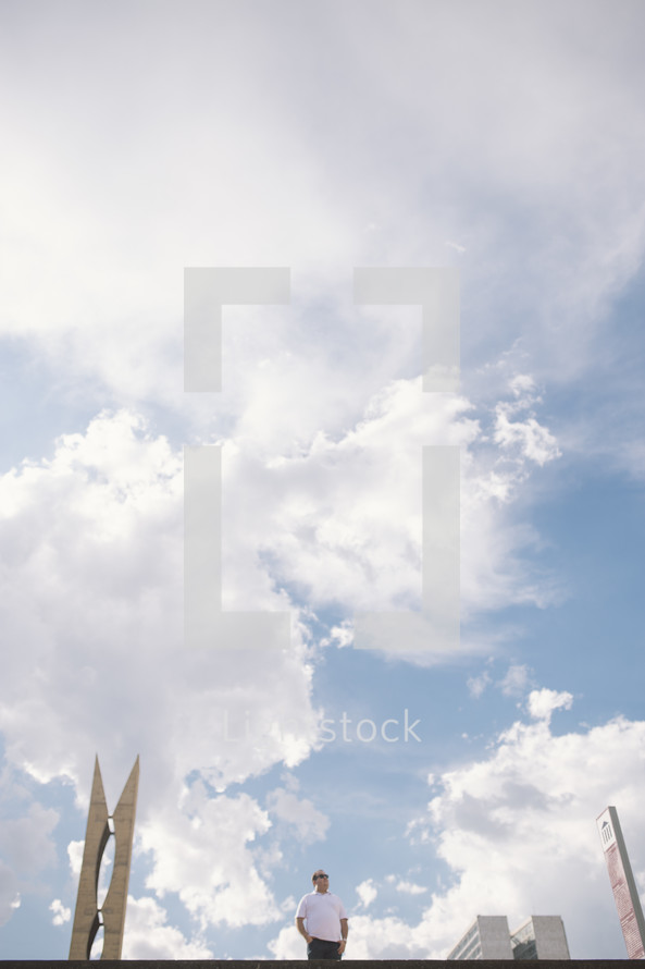 man standing in a city under blue skies