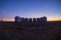 group of silo's on a farm at sunset