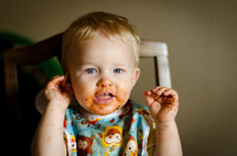 a messy toddler boy in a bib
