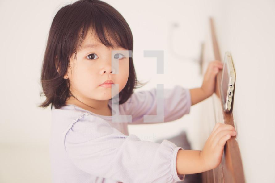a toddler girl watching a cellphone screen