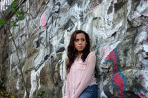 Girl standing against a graffiti-covered stone wall.