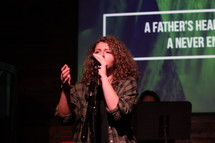 a woman singing into a microphone at a worship service