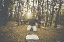 a man kneeling in front of a Bible in the forest praising God