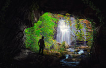 silhouette of a man standing at the mouth of a cave and a waterfall