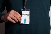 A man wearing a volunteer badge.