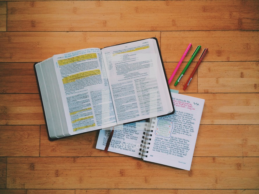 open Bible, journal, and pens on a wood floor