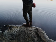 man standing on a rock at the edge of a lake