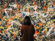 woman looking at a painting of paint splatter