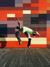 Two people doing back flips in front of a colorful wall.