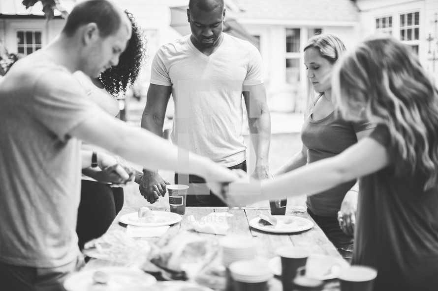 holding hands in prayer above a table at a cookout