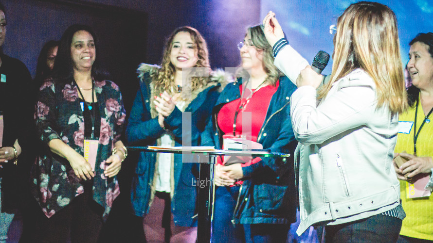 group of women standing on stage during a worship service