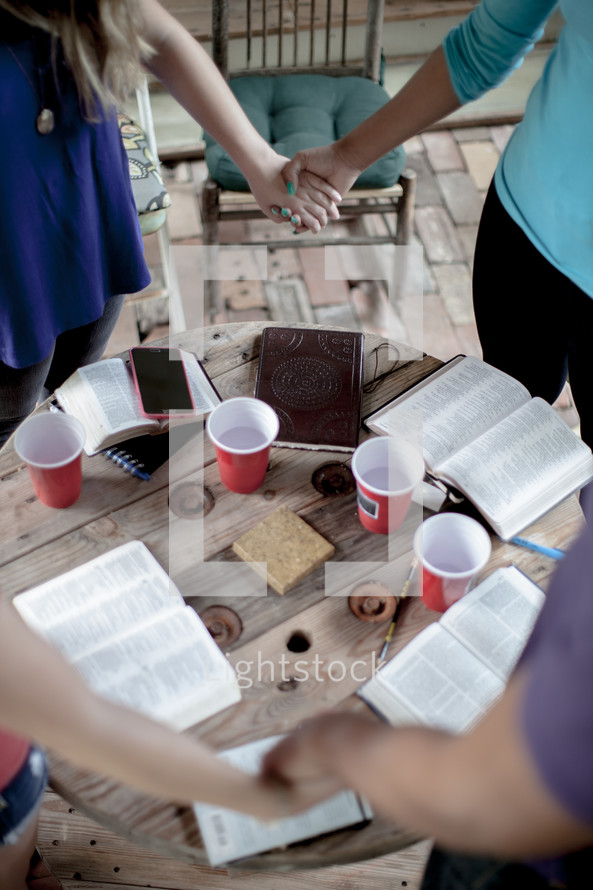 holding hands in a prayer circle over open Bibles
