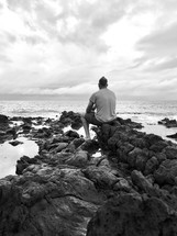 man sitting on rocks along a shore